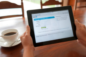 Woman holding an ipad showing the Linkedin login screen