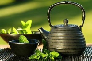 Black iron asian teapot with sprigs of mint for tea