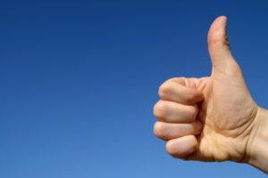 Thumbs up with blue sky background and space for text.