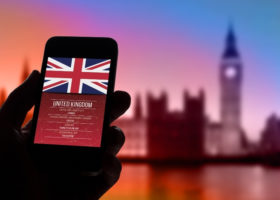 Hand holding mobile phone with UK flag and Big Ben in the background